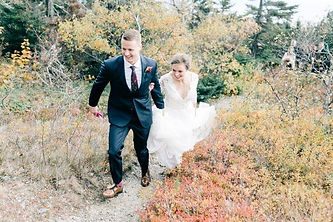 Bohemian bride and groom strolling through forest path.
