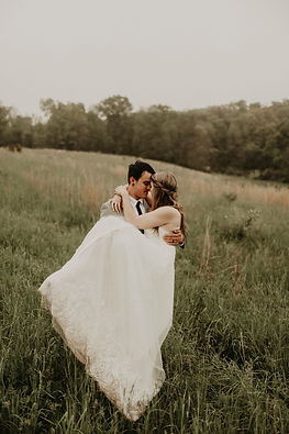 Groom carrying his bohemian bride in a grassy field.