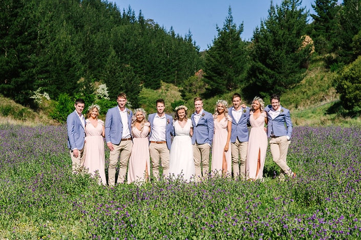 Bohemian wedding party in lush field.