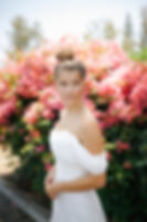 Bride with her hair in a bun in front of bougainvilleas.