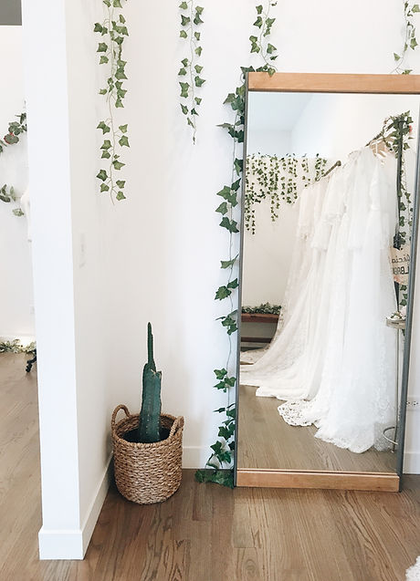 Mirror in wedding dress fitting room with reflection of wedding dresses on racks next to decorative cactus.