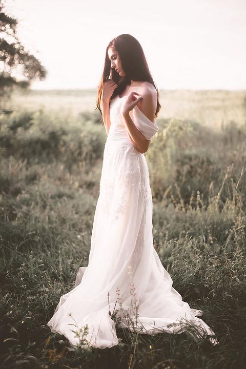 Side view of boho bride in grassy field.