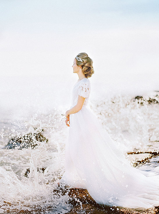 Bride wearing a crown in a beautiful bohemian wedding dress while the ocean's waves crash against the rock on the shoreline that she is standing on.