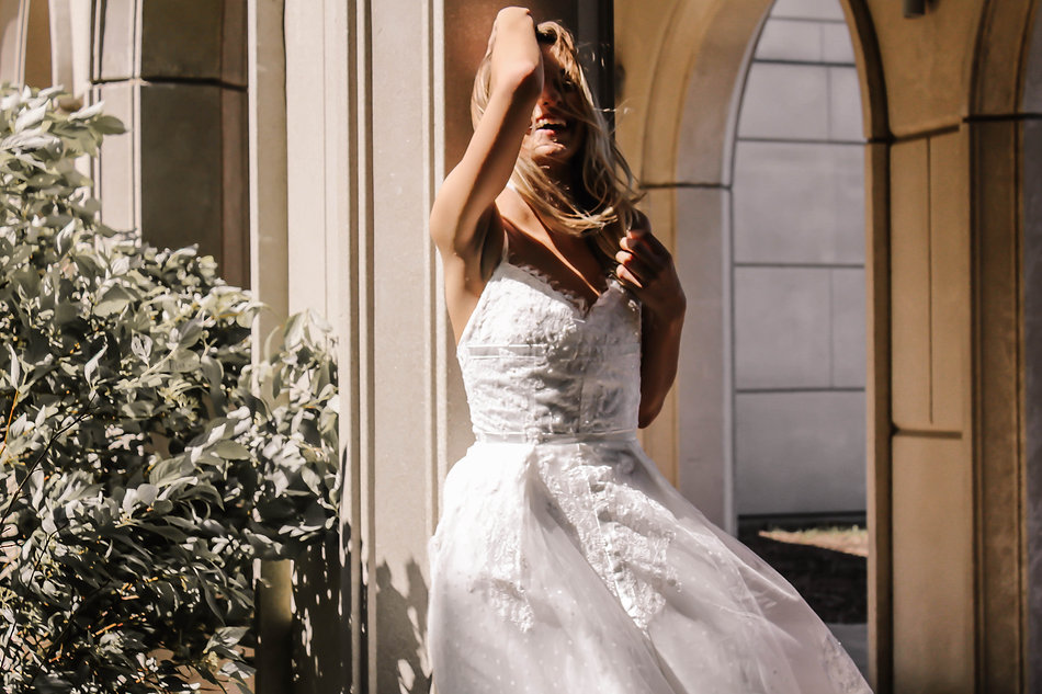 Bride running her fingers through her hair with her back to a stone pillar.