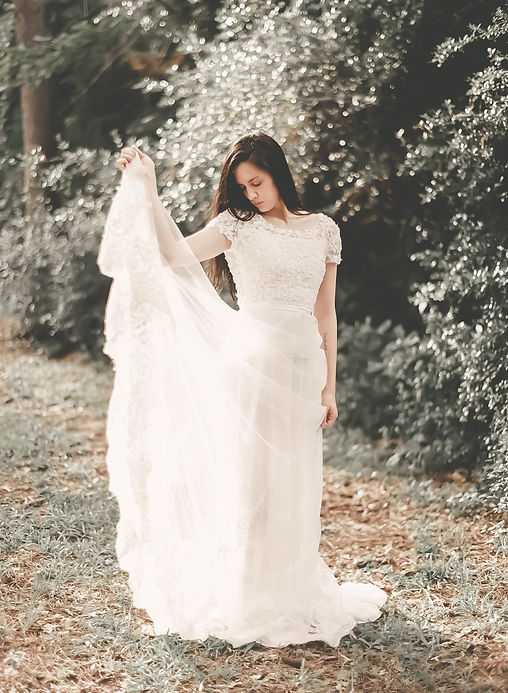 Bride holding out the skirt of her bohemian wedding dress.