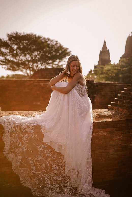 Full side view of a bride sitting on top of an ancient wall while wearing a boho wedding dress.