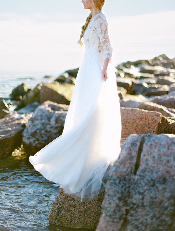 Boho bride looking out towards the water whle perched atop a rock and looking stunning in her boho wedding dress.
