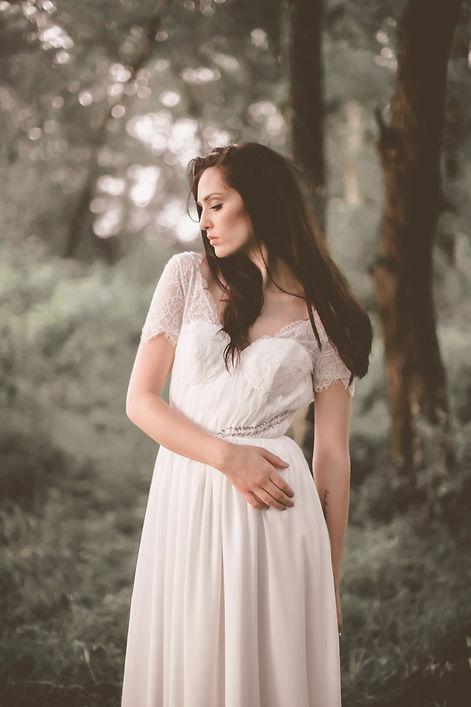 Dark haired  bride in bohemian wedding dress in a forest.