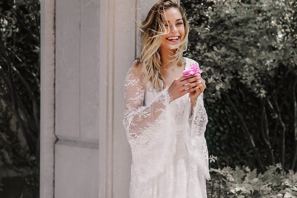 Bride with natural smile holding a pink flower in the Primrose boho bridal gown.