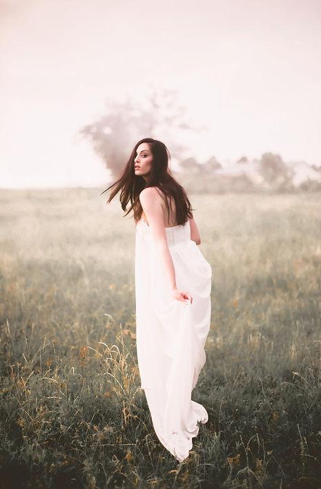 Brunette bride in a boho wedding dress in a grass field.