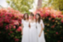 Three Flora & Lane brides in front of backdrop of beautiful fully bloomed bougainvilleas.