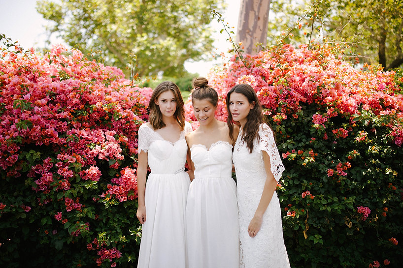 Three Flora & Lane brides wearing beautiful boho wedding dresses in front of backdrop of beautiful fully bloomed bougainvilleas.