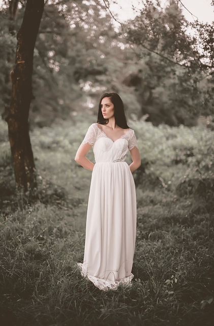 Bride with a fierce pose in the woods in her Flora & Lane wedding gown.