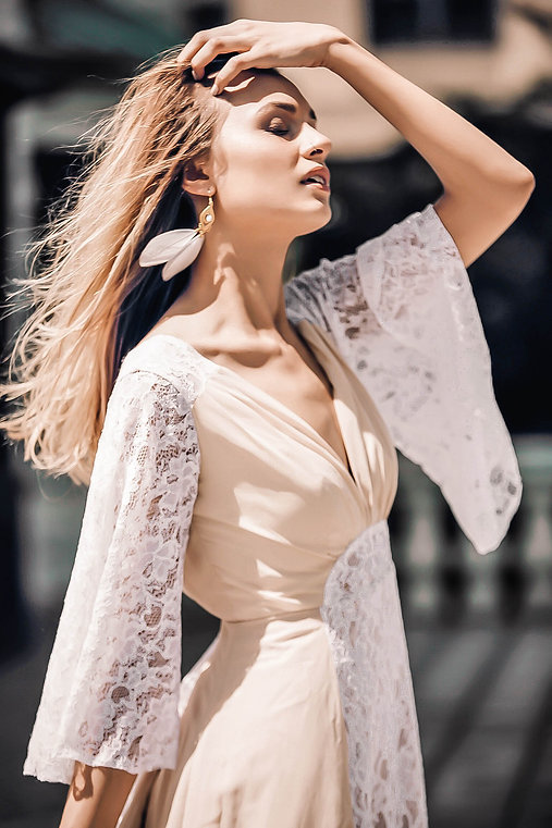 Bride in the Lavie boho bridal gown running her fingers through her hair across her forehead as the wind blows her white feather earrings.