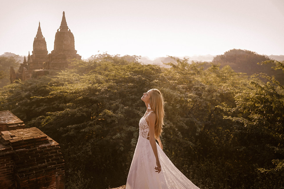 A bride in a boho wedding dress basking in the sun with two ancient stupas as a backdrop.