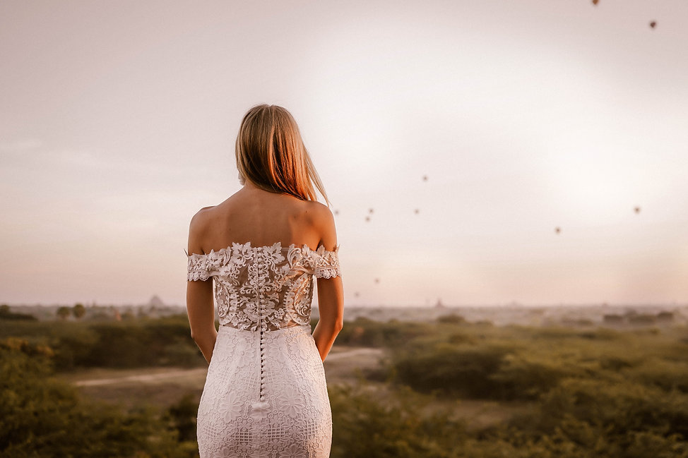 Back view of a bride looking out towards floating hot air balloons displaying the intricate details of her lace wedding dress.