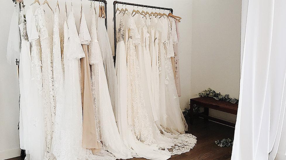 Wedding dresses on racks in Flora & Lane fitting room.