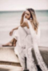 Girl in wedding dress posing next to lake.