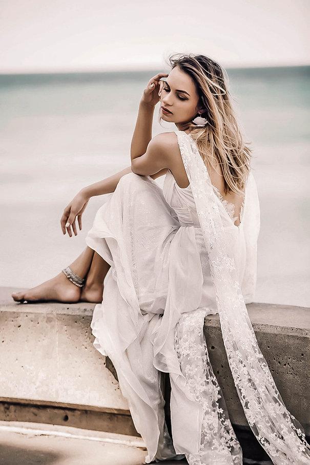 Girl in boho wedding dress posing next to lake.