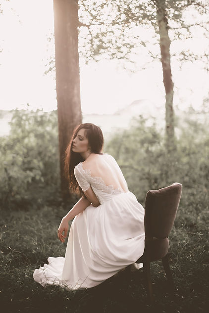 Bride sitting in a upholstered chair in the middle of the woods while in her bohemian wedding dress.