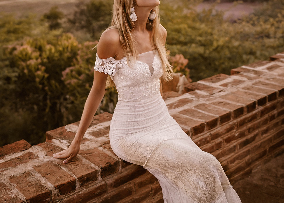 Close up picture of a sitting bride wearing the Moonlight dress by Flora and Lane.