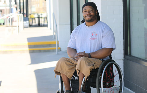 A man in a t-shirt and khaki shorts sitting in his wheelchair smiling