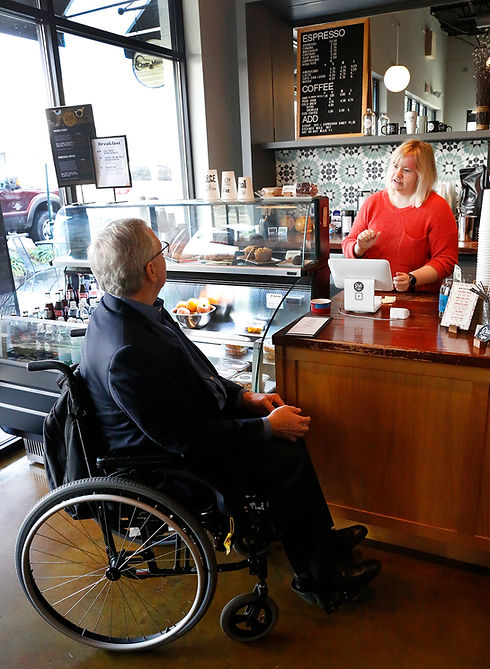 Man in a suit using a wheelchair speaking to a cashier at a coffee shop - Photo by Eichner Studios