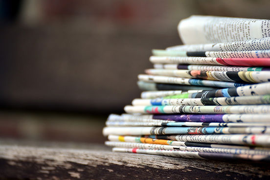 Hintergrundbild der Presseübersicht mit diversen Zeitungen übereinanderliegend