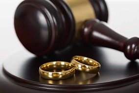 Pair of gold rings resting on a sound block in front of a gavel