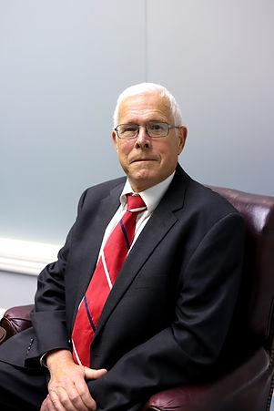 John M. Crossett seated in leather chair