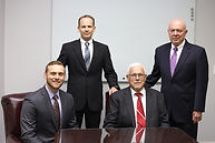 Four attorney's standing or sitting aroud a glass table