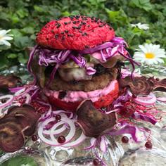 Komplett violett; der low carb Burger. Schweizer Rindfleisch im Randen-Bun aus Kokosmehl, gekochtem und rohen Rotkraut, Mozzarella und eine Sauerrahm-Cranberrysauce. Dazu Randenchips, Randenkaviar, Sprossen und violette Zwiebeln
