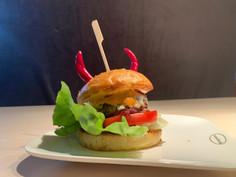 Spicy Devil aus selbstgemachtem Burgerbun, einer selbstgemachten Chilisauce, Salat, Rotweinzwiebeln, selbstgemachtem Burgerpattie, Emmentalerkäse und der Teufelssauce