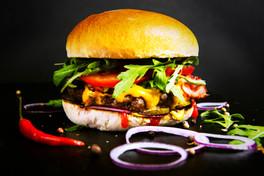 Grilleria Luxo – 100 % Schweizer Rindfleisch, schmelzender Cheddarkäse, knusprige Speckstreifen, Rucola, Tomaten, Bun, Essiggurken und rote Zwiebelringe