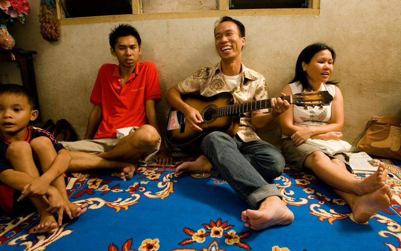 four people-most likely a family- are shown on a blue carpet singing, the older man-or father- is playing the guitar whilst laughing