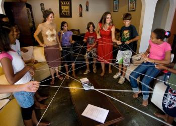 multiple girls are shown standing around making a web, each women are different ages