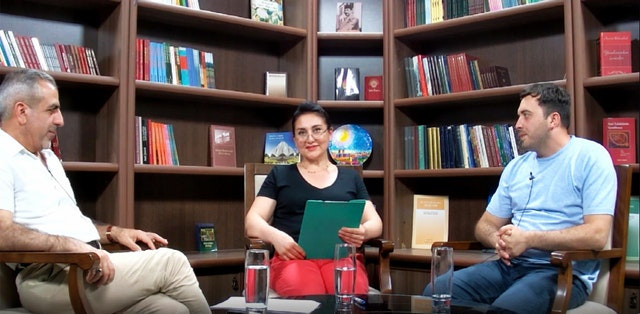 three people are shown sitting around a table in front of a bookshelf with individual glasses of water in front of them. the lady is sitting in the center with a green clipboard