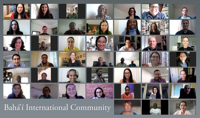 pictures of each of the baha'i international community are shown on a grey background, the group is very diverse and are all smiling.