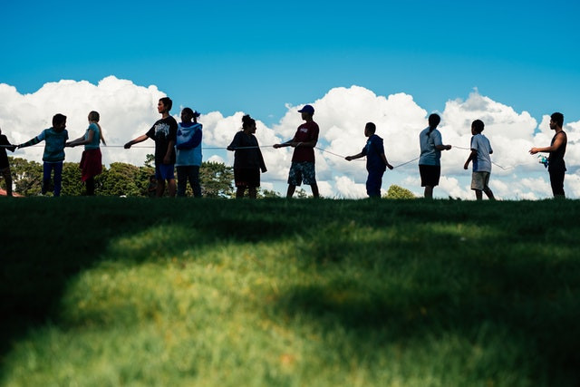 multiple people are shown on the top of a small green hill holding a rope in one line