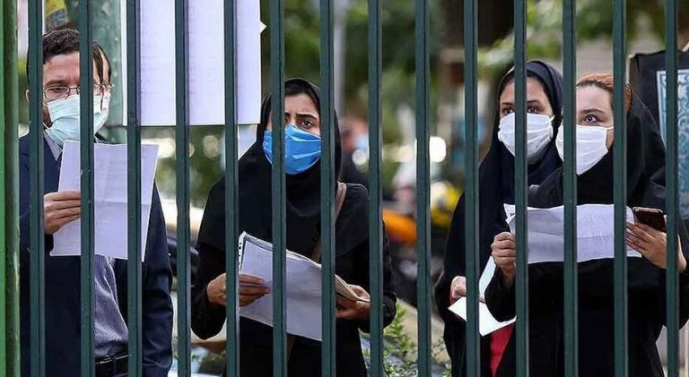 four people are shown standing with papers behind a gate