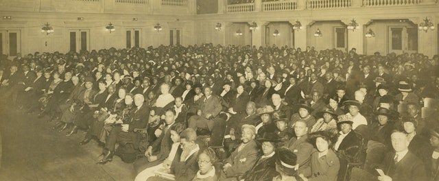 an image of an old conference is shown, the image is very yellowed from age