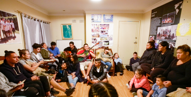 large group of baha'is sitting in a circle, with the younger children and youth on the ground, one person is holding a guitar