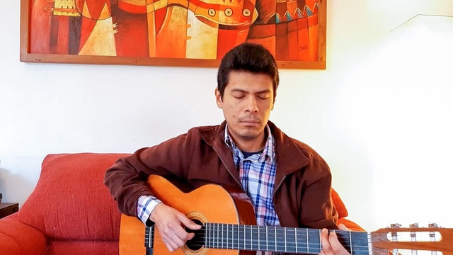 man playing guitar on a red couch with his eyes closed