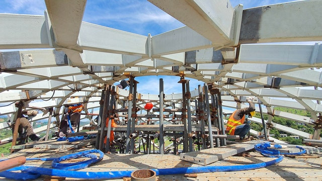 an image of construction workers working on the top of the dome