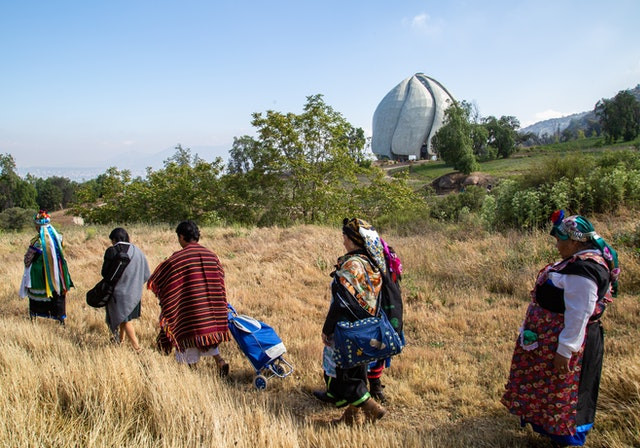 5 women are walking in brown grass, a short distance away from the Baha'i house of worship in Chile.