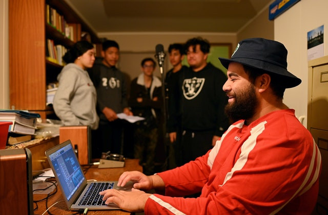 a man in a red longsleeve shirt and brown beard, wearing a black hat is shown smiling at a laptop on a cluttered desk, with 5 people standing in the background around a microphone