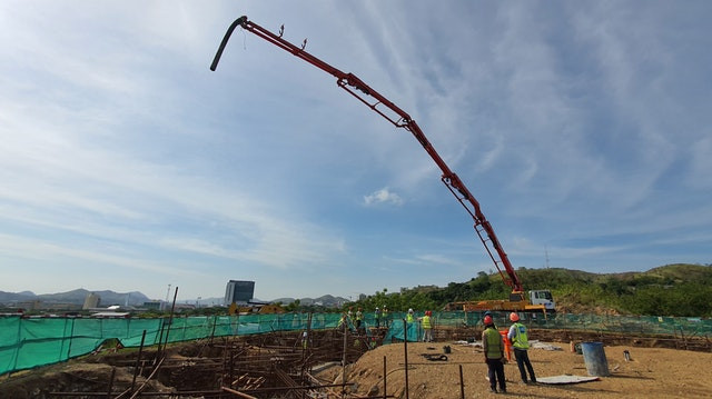 The concrete boom pump stretches high in the sky.