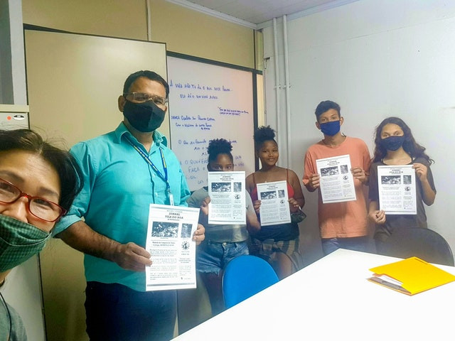 6 people are shown, four of which are youth, two are the facilitator, all of them are holding up a sheet of paper with information regarding the clean-up