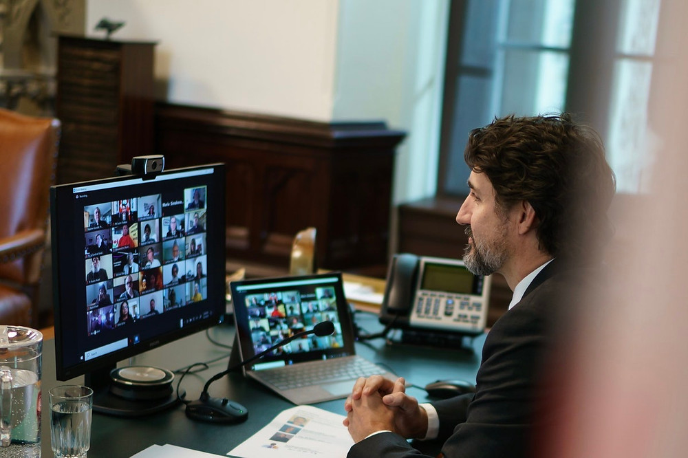 Justin Trudeau is shown smiling in front of a computer and laptop on a zoom call with many participants