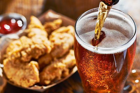 pouring beer into mug with fried chicken